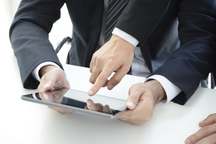 Two businessmen using tablet computer with one hand touching the screen - business discussion concept